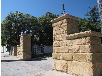 Sandstone gates leading into peaceful Junipero Plaza.