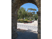 Looking through Junipero Plaza archway to the mission rose garden.
