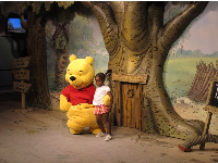 A little girl greets Winnie the Pooh.