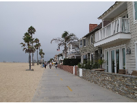 The beach boardwalk between houses and sand.