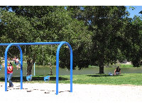 Swings in a lovely spot by the lake, with sand underneath.
