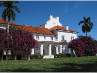 Side view of the mansion and trellis overflowing with bougainvillea.