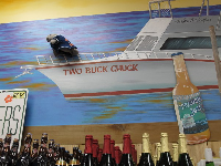 A manatee stuffed animal is hidden on the wall by the Two Buck Chuck ($2.99 Charles Shaw wine).