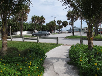 Walking path with flowers on either side, leading into the parking lot.