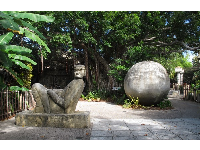 Geometric ball sculpture and man reclining- these are found in the Yucatan.