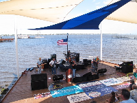 A band plays at the stage surrounded by water on all three sides.
