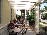 The Starbucks at Sea Plum Town Center has outdoor seating surrounded by bright tropical foliage.