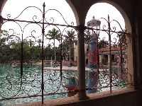 Looking through the entry building at the pool. Archways and pink wrought-iron.
