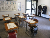 Japanese school classroom, with desks, charts, and uniforms.