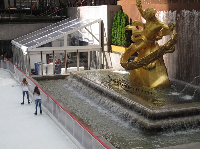 Two girls ice skate past the golden statue.