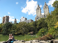 Friends sit on the rocks beside The Lake, with the apartment buildings of Central Park West soaring behind them.