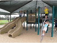 The fun play structure under a huge shade canopy.