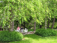 A family enjoys a picnic at a shady table in the gardens.