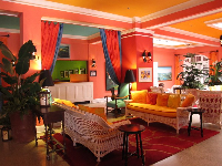 The richly colored interior of the Colony Hotel with original wicker furniture, palms, and iron candelabras.