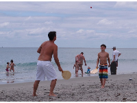 Father and son play paddle ball at the shoreline.