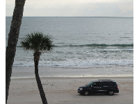 A mini-van driving along the beach.
