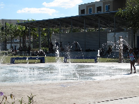 Water play at the splash pad. Behind, the amphitheater provides shade for parents.
