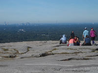Hikers gather to watch the city skyline.