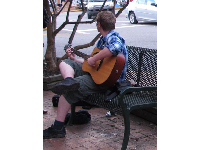 A student plays guitar as cars go by at the town square.