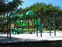 The bright green playground with twisty slide, baby swings, swings, and sandy floor.