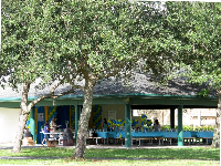 A party in a pavilion across the grass from the playground.