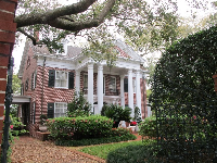 Historic brick mansion and large tree.