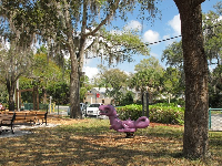 Purple dinosaur bouncy, picnic tables with chair backs, and trees for shade.