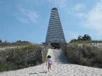 A girl runs up the sand to the tower.