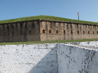 White wall of Spanish fort, with main fort behind.