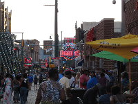 Crowds fill the street in the early evening.