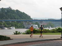 Joggers enjoy a run beside the river.