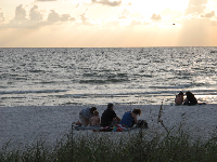 People gather on the beach to enjoy the sunset.