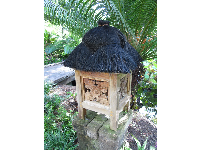 Thatched spirit house in the Southeast Asian garden.