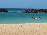 Snorkelers enjoy the little cove sheltered from surf by rock walls.