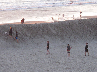 Guys playing soccer behind the wall of sand.