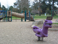 The dinosaur, toddler playground, and swings, near the Waller Lane entrance.