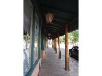 Shady walkway in front of historic storefronts.