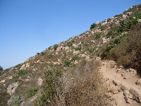 The hiking path goes through a boulder-strewn landscape.