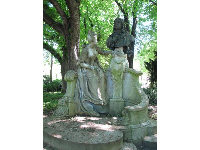 Monument to Jean-Antoine Watteau, surrounded by leafy trees.