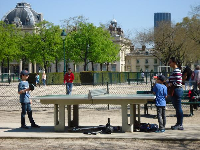 A family plays ping pong at the park.