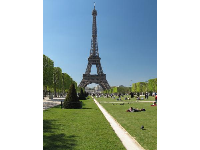 People laying on the lawn in the Champ de Mars, with views of the Eiffel Tower.