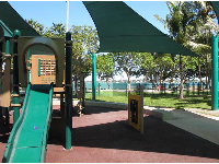 Playground with views of palm trees and water.