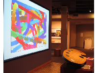 A child paints and watches her creation on the giant screen.