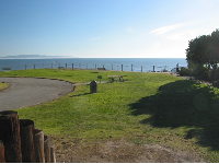 Sloping lawn and ocean views, picnic tables and benches strategically placed.