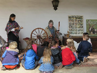 A school group watches a spinning demonstration at the presidio.