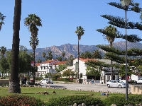 View of mountains, Norfolk pine, and palm trees at little park by the train station.