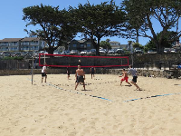 Men playing sand volleyball above the beach.