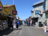 Tourists walk beside the stores on the wharf.