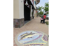 Tiled mosaic on the sidewalk.