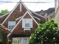Gingerbread-style house with mountains behind, plus plumeria tree.